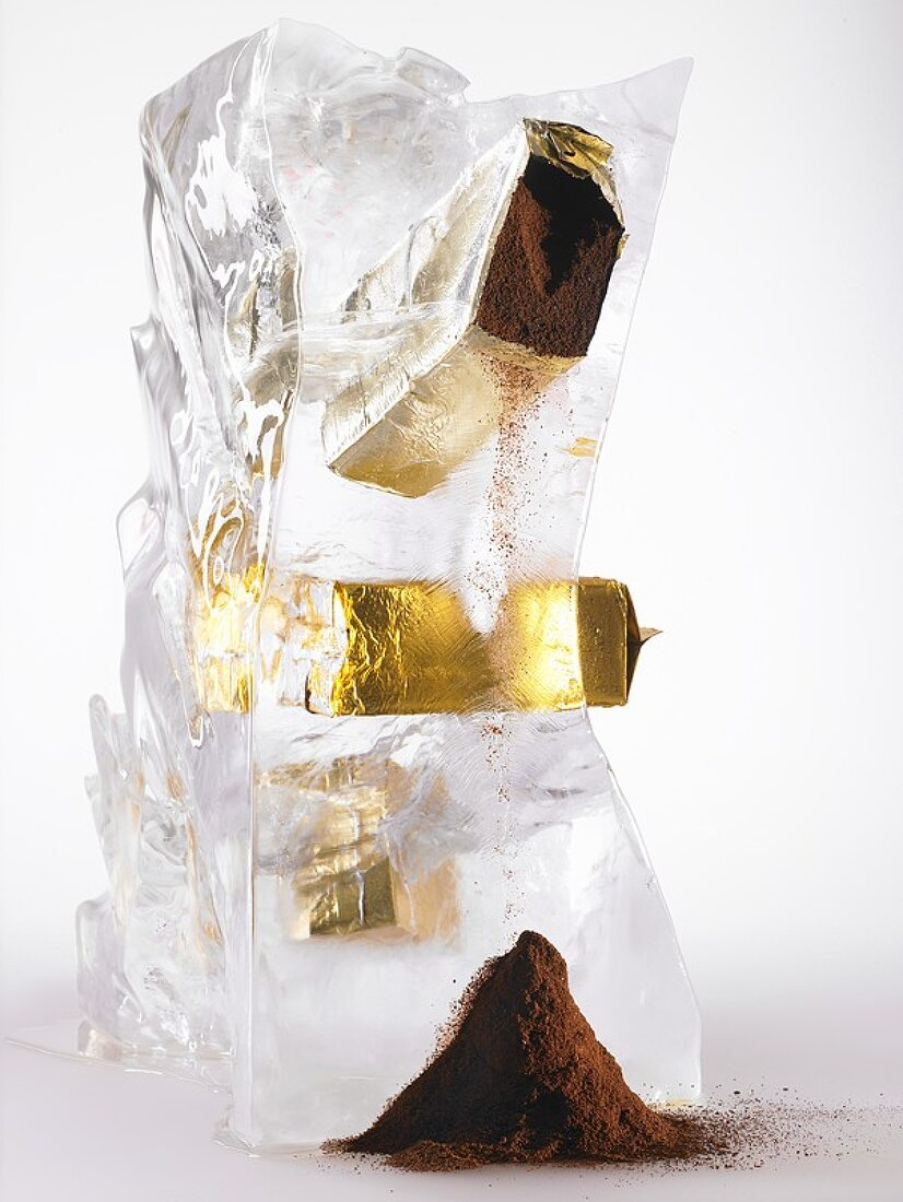 Ground coffee in a block of ice trickling out of packet