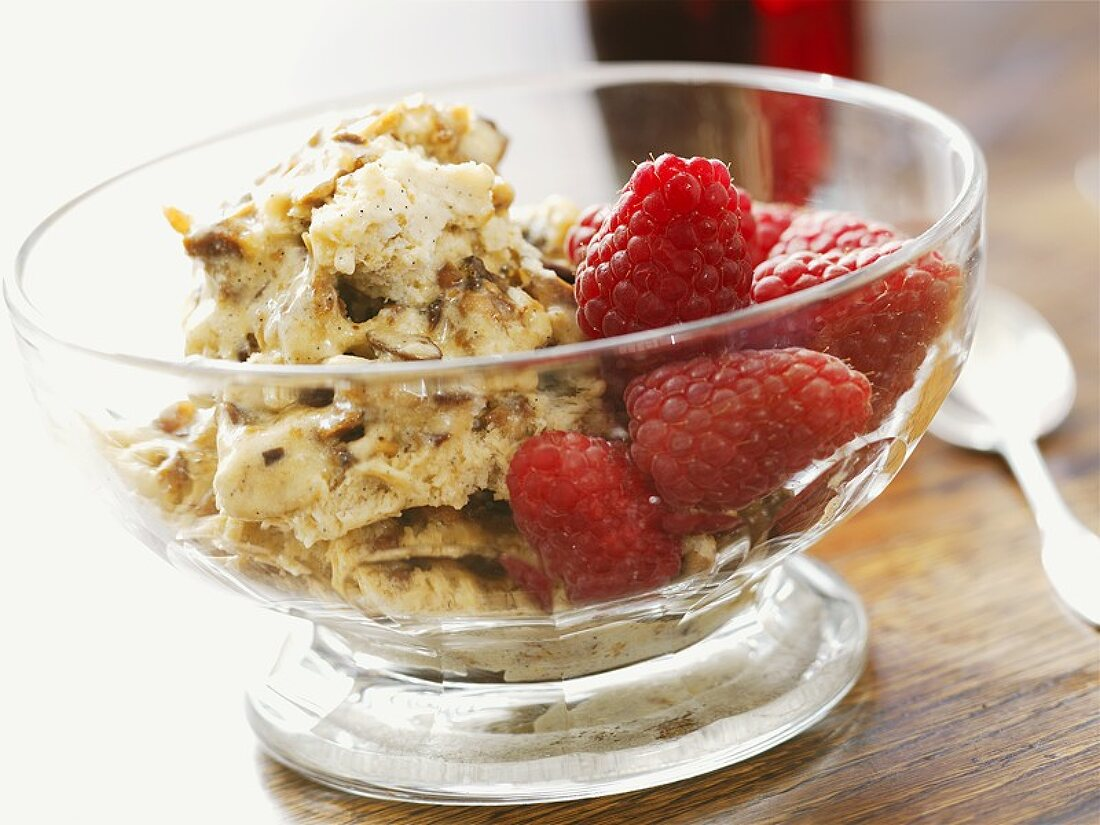 Nougat ice cream with raspberries in a small glass bowl