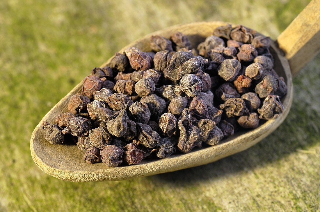 Dried schisandra berries on a wooden spoon