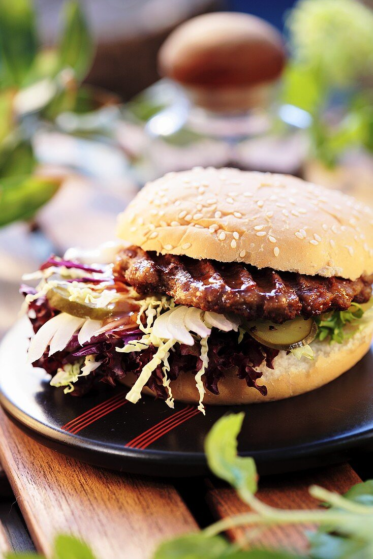 A hamburger with lettuce, cabbage and gherkin slices