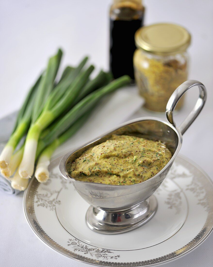 Mustard sauce in a sauce-boat with a few ingredients