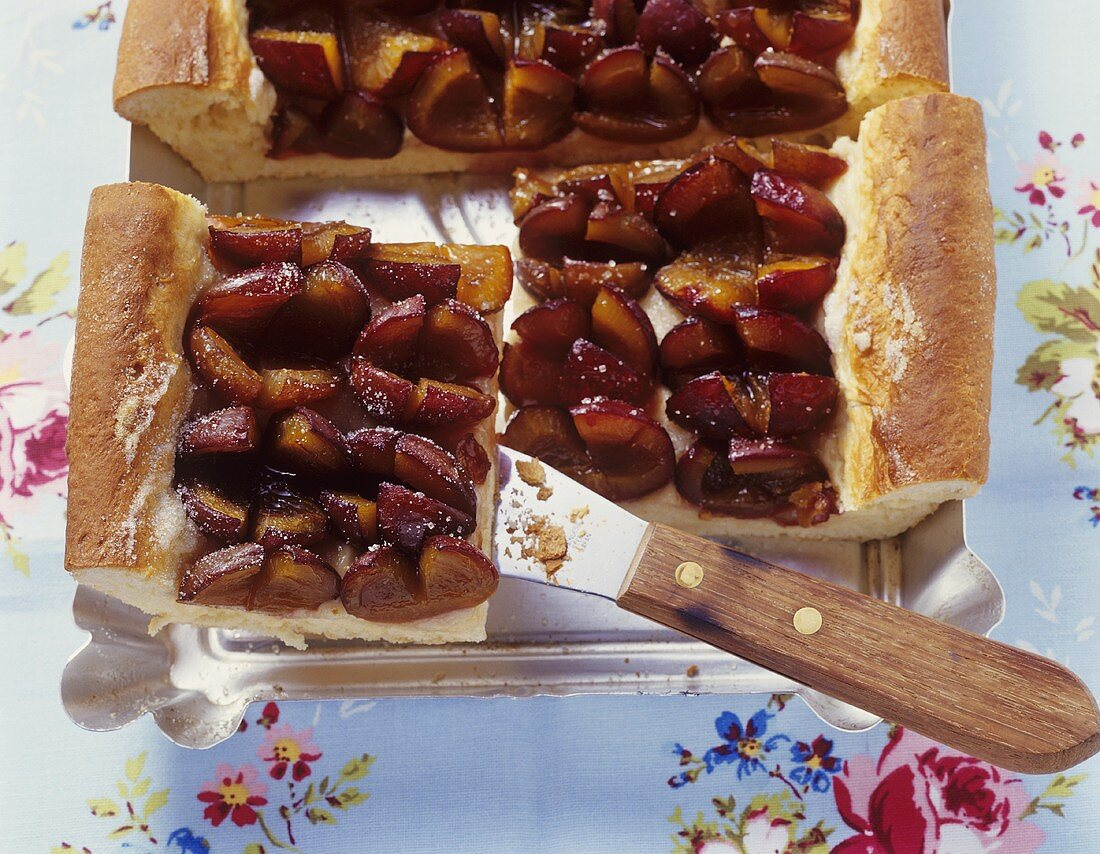 Tray-baked plum cake, pieces cut