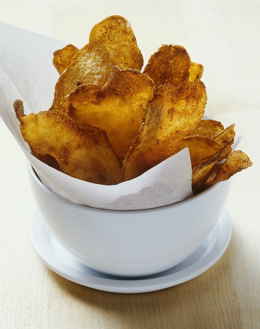 Home-made paprika crisps with baking paper in a bowl