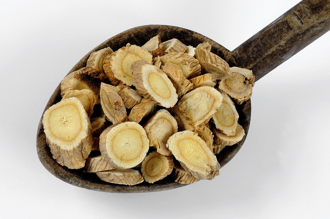 Slices of astragalus root on a wooden spoon