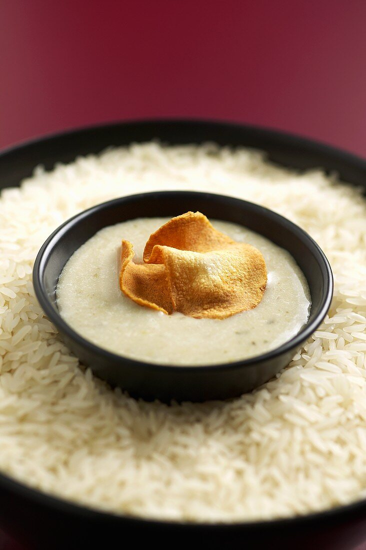 Jerusalem artichoke soup and crisps in bowl on rice