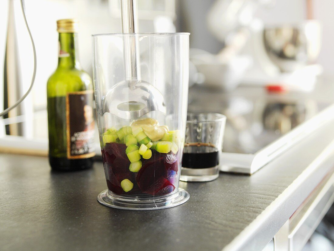 Green asparagus and beetroot in a beaker with hand blender