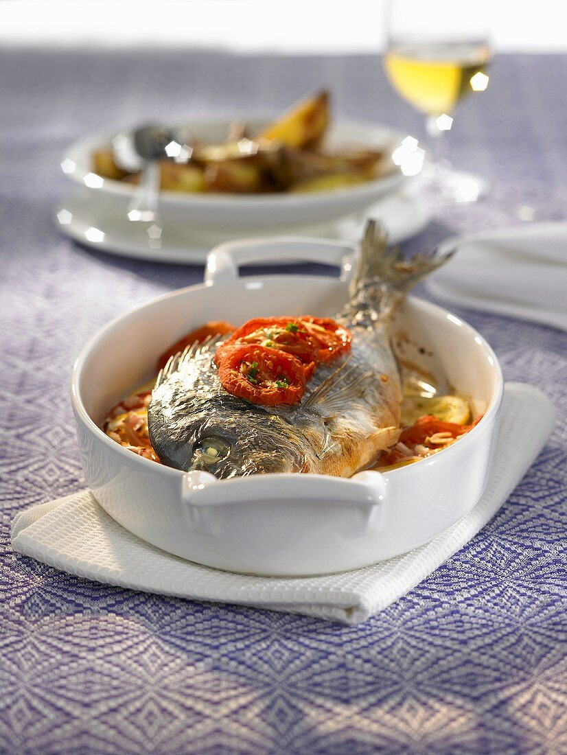 Oven-baked bream with tomatoes, onions and white wine