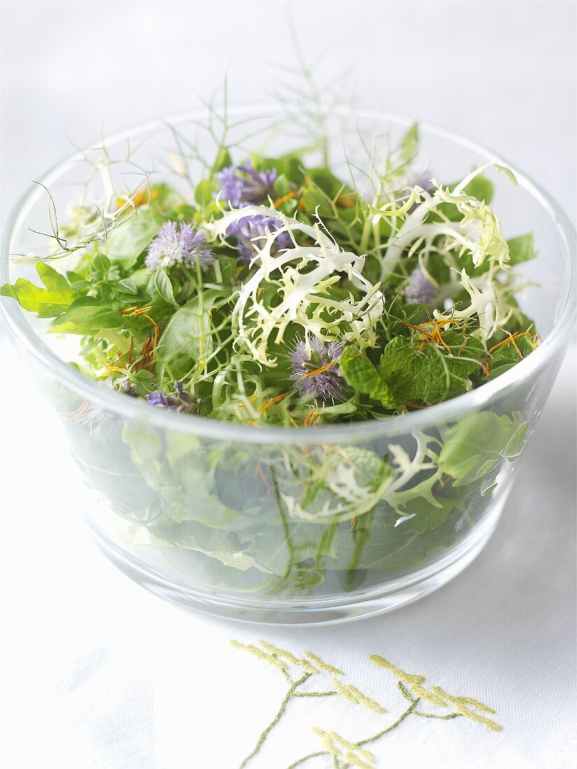 Herb salad with edible flowers in a glass bowl