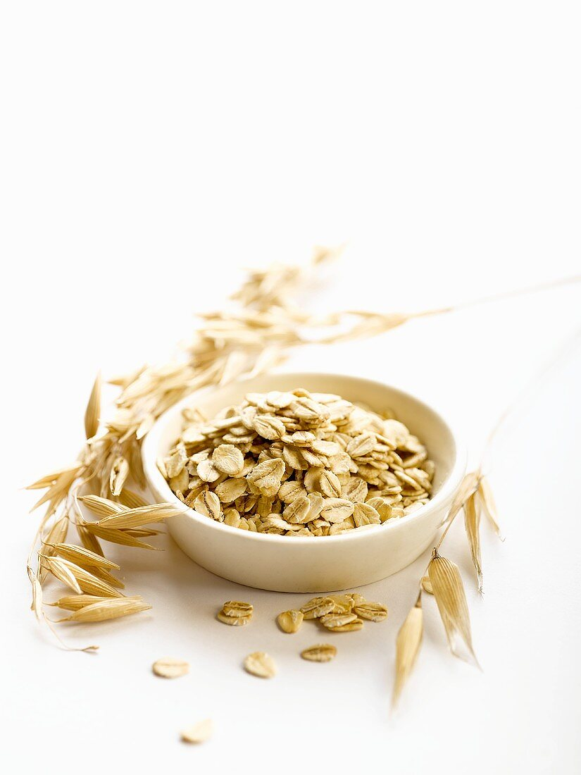 Rolled oats in a small dish and ears of oats