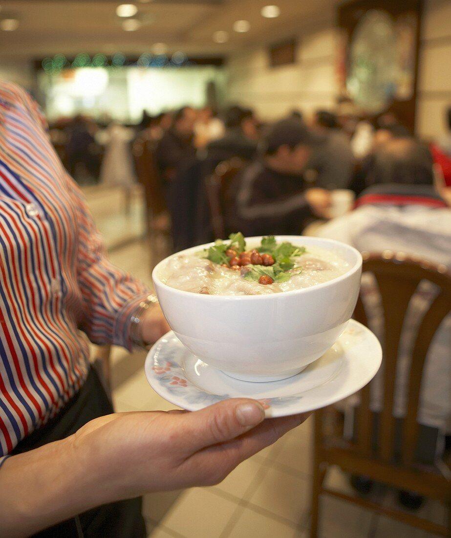 Woman serving a bowl of congee (rice porridge, China)