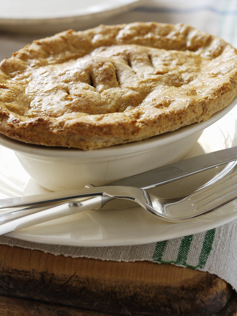 Beef pie in a pie dish with knife and fork