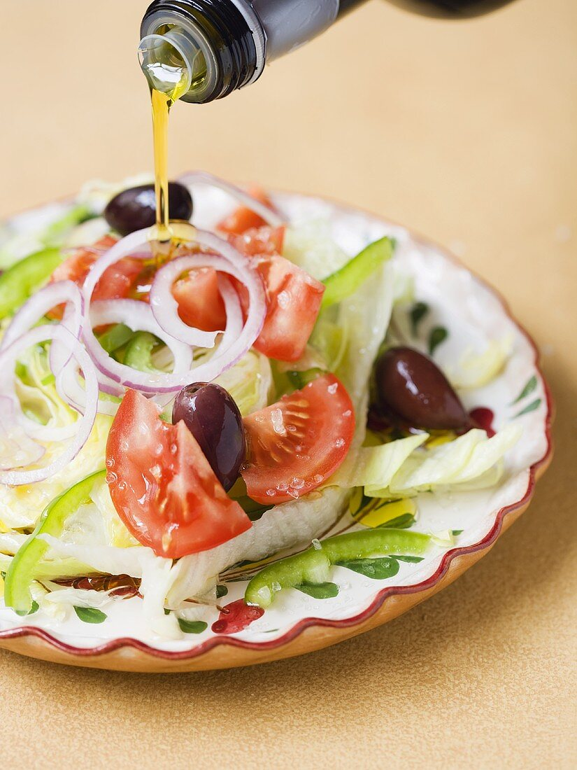 Olive oil being poured over Mediterranean salad