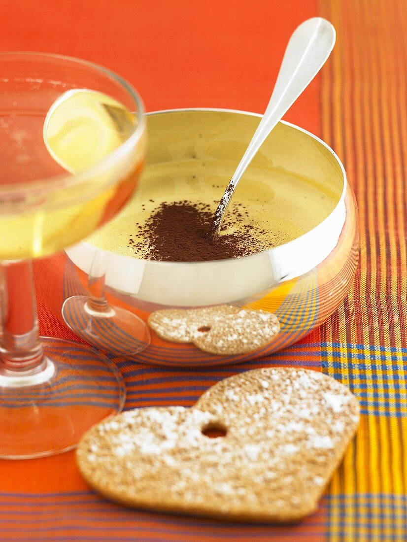 Orange sabayon in silver bowl with cocoa powder & biscuit