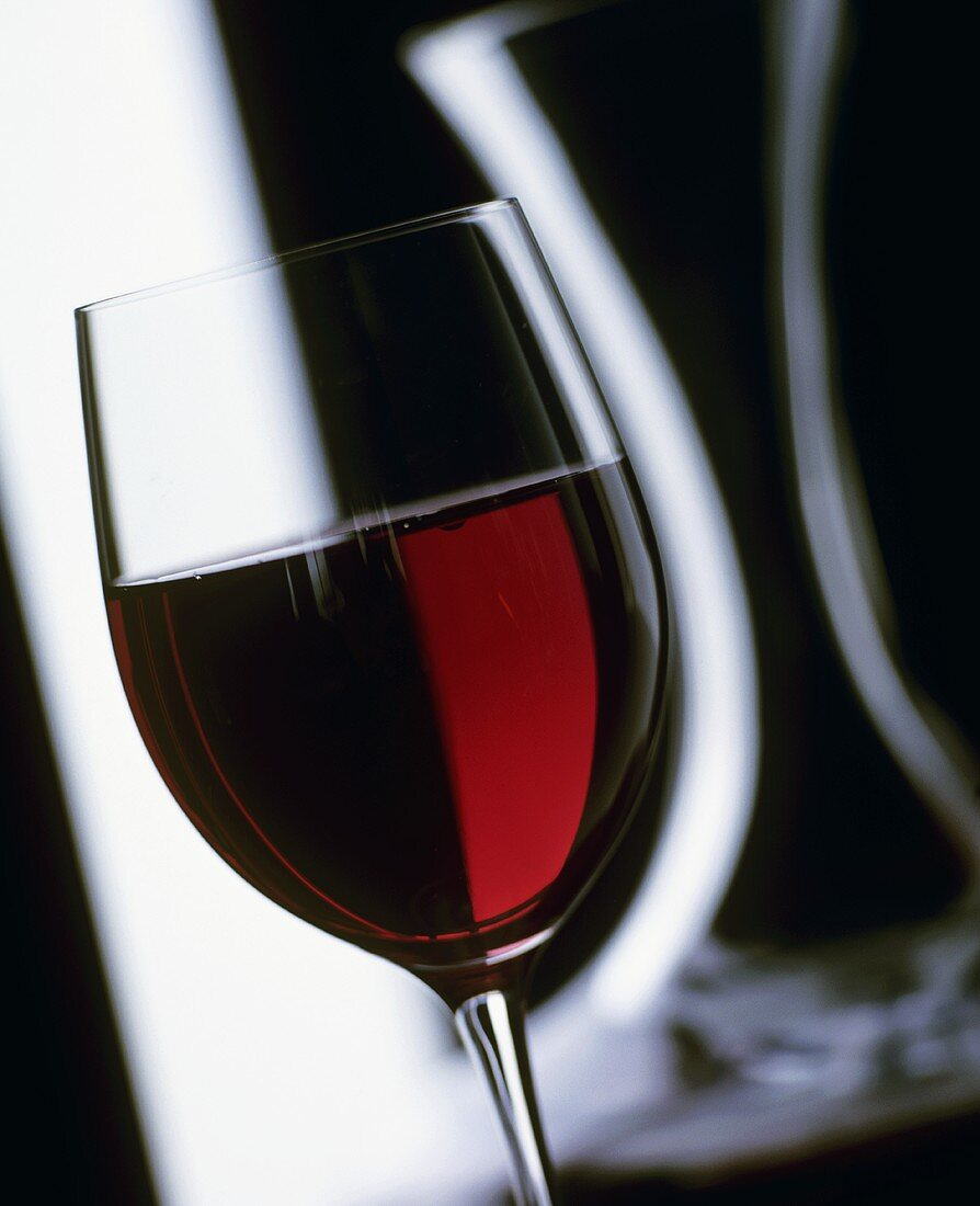 A glass of red wine with carafe