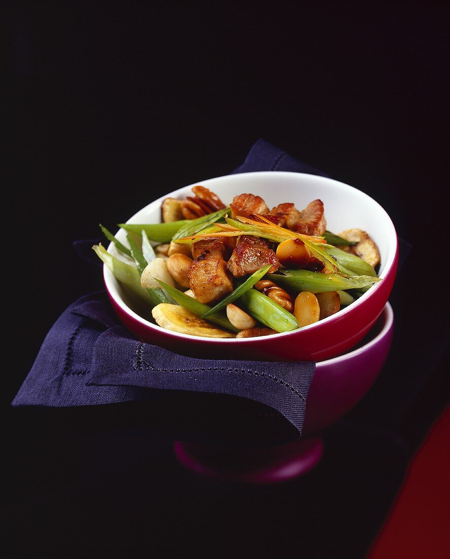 Sweet and sour belly pork with vegetables, bananas and nuts