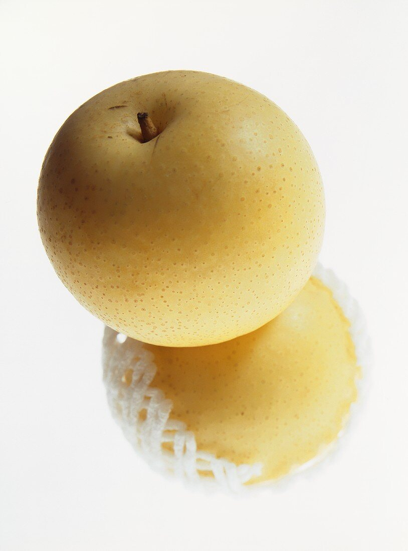 Two nashi pears, one in net
