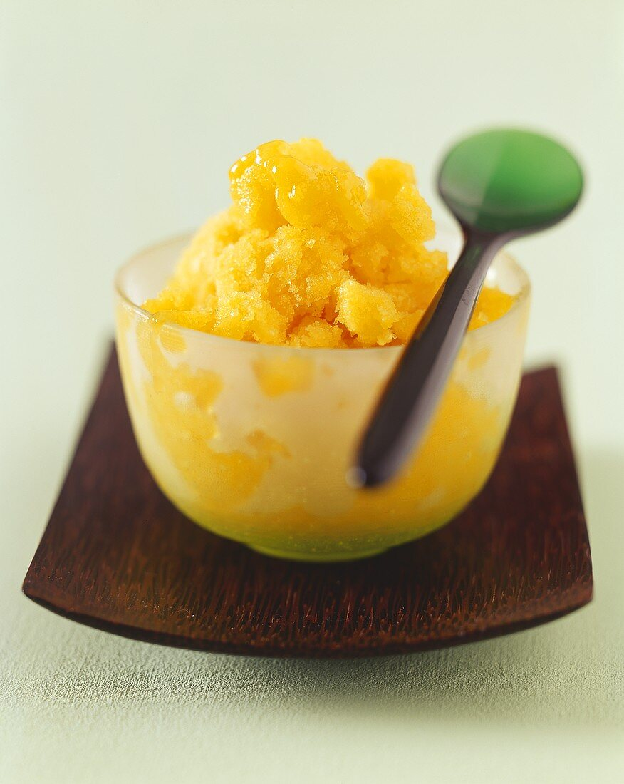 Mango sorbet in a glass bowl with spoon