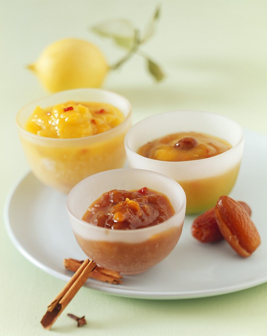 Three different mango chutneys in small glass bowls