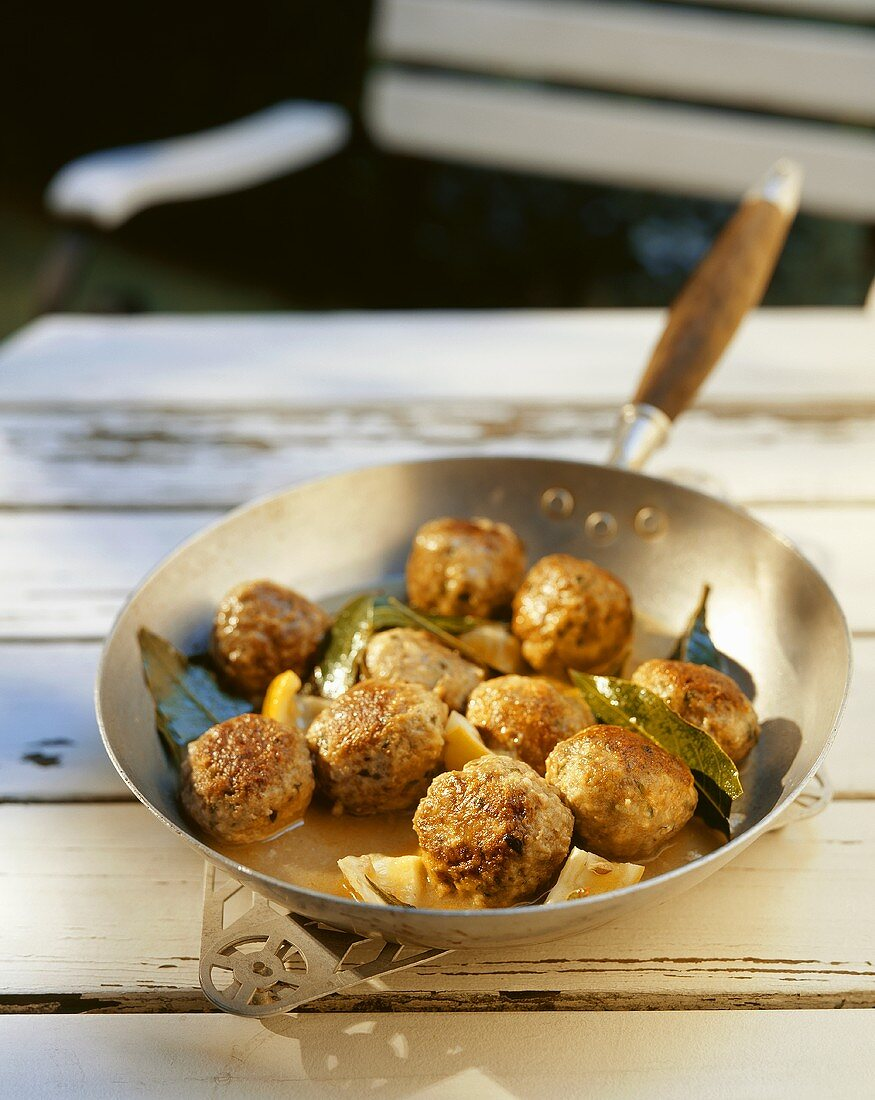 Meatballs in lemon and bay leaf sauce in a frying pan