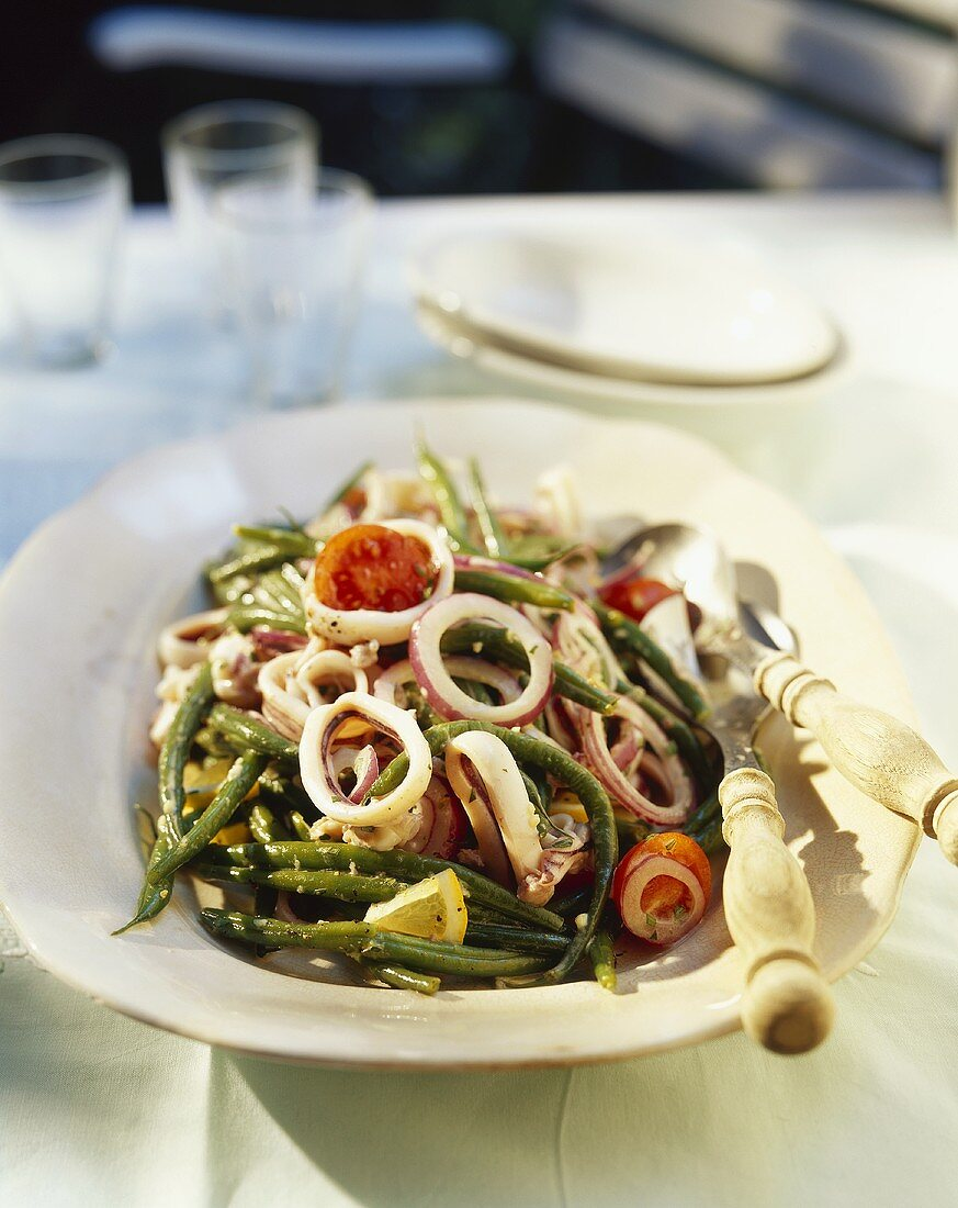 Squid rings with beans, tomatoes and lemon