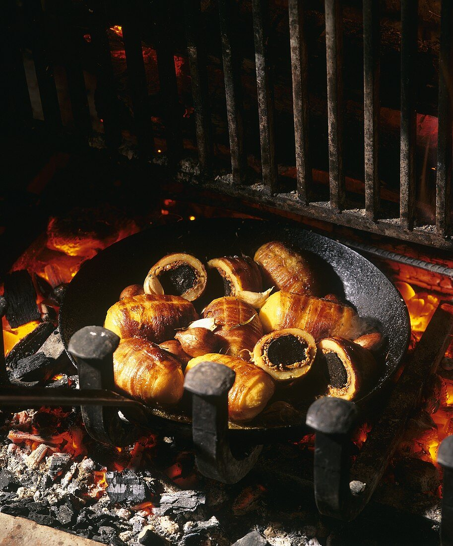 Bacon-wrapped potatoes stuffed with truffles over fire