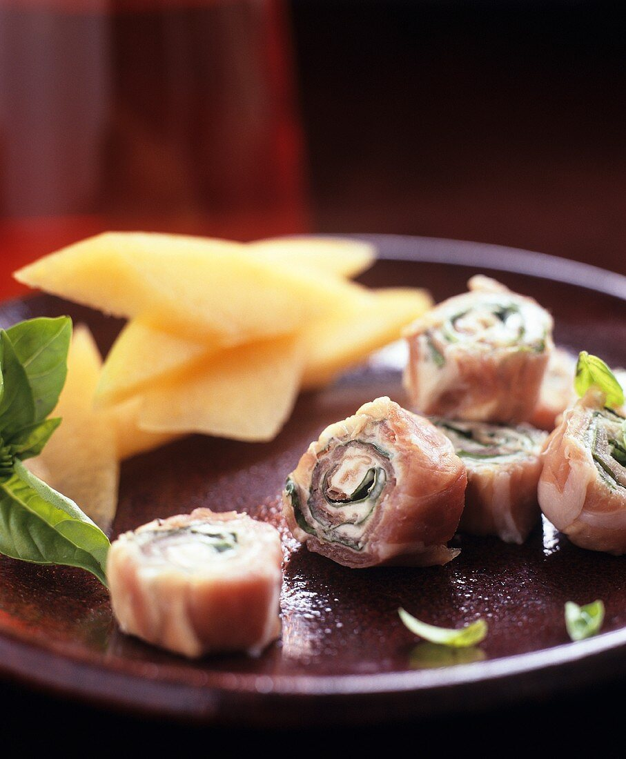 Ham and soft cheese rolls with basil and melon