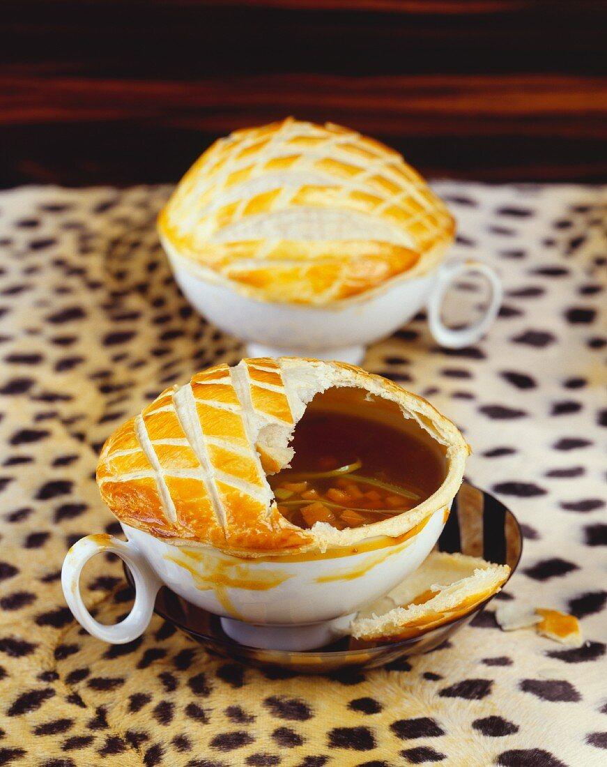 Two bowls of vegetable soup with puff pastry crust