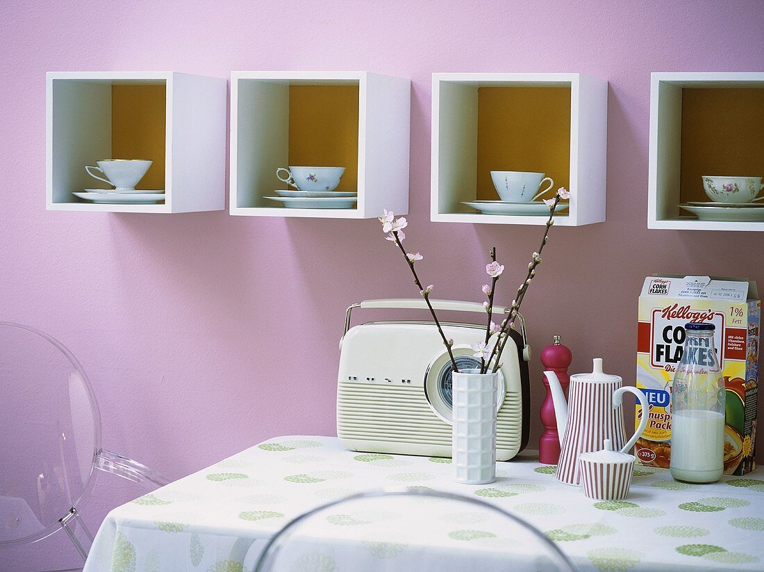 Old cups and saucers on modern shelves in kitchen