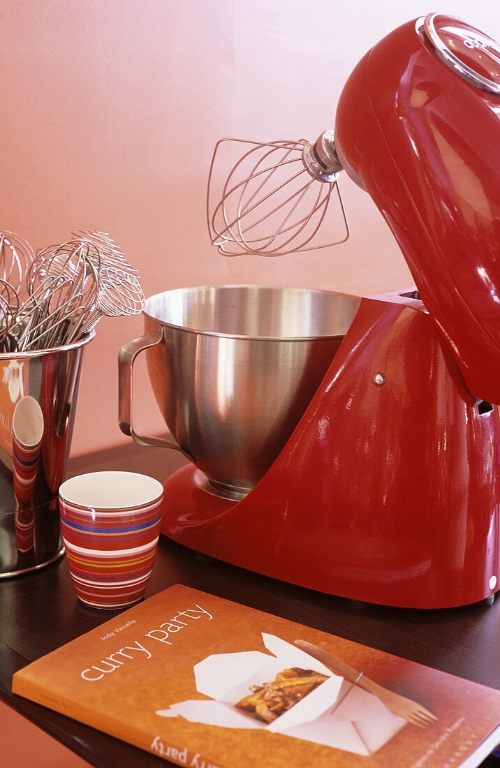 Electric mixer with whisk, cookery book