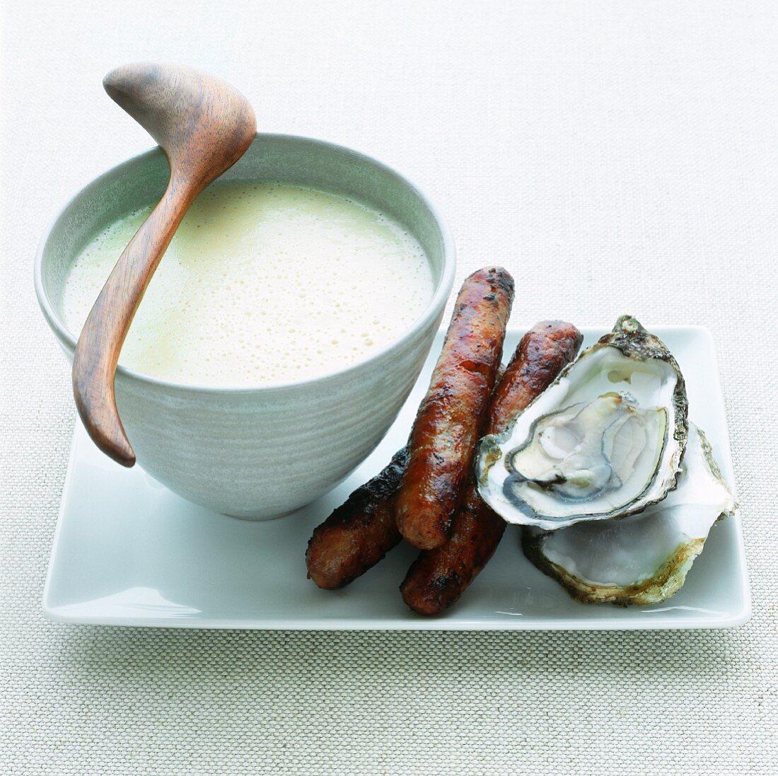 Oyster soup with sausages and fresh oysters