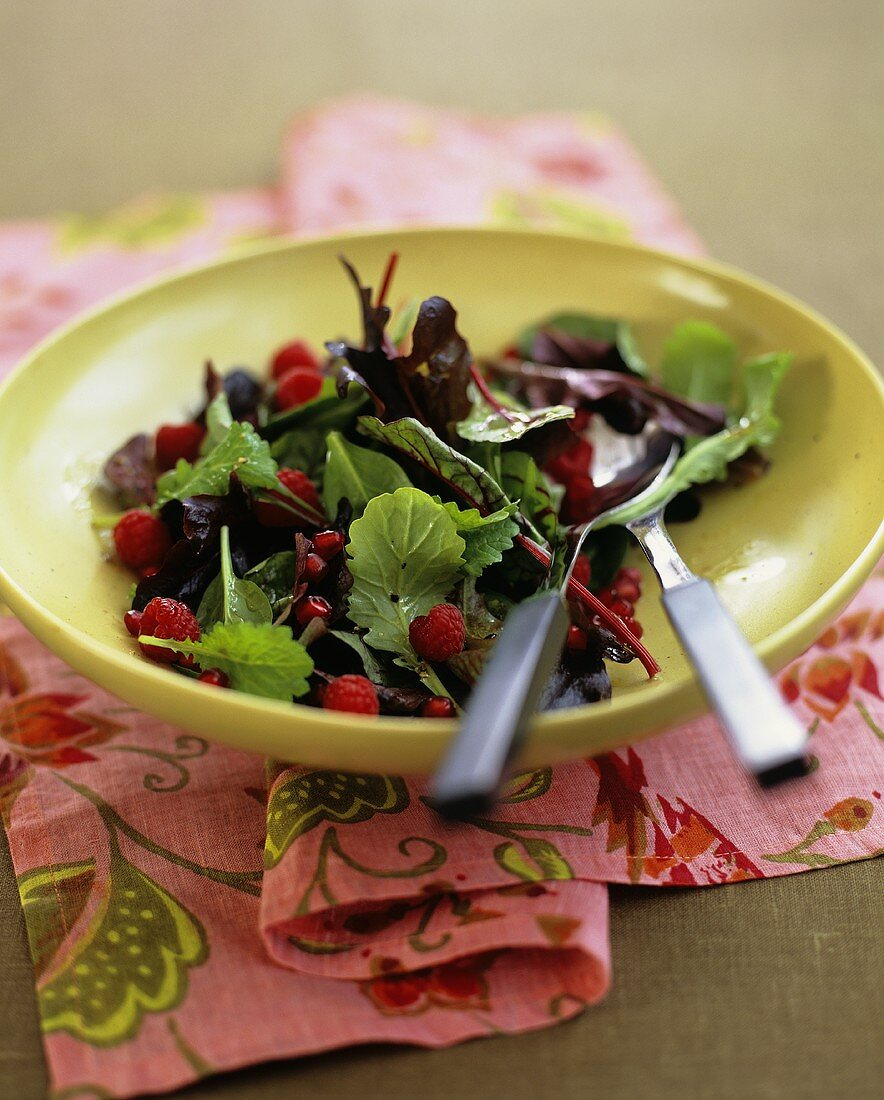 Salad leaves with pomegranate seeds and raspberries