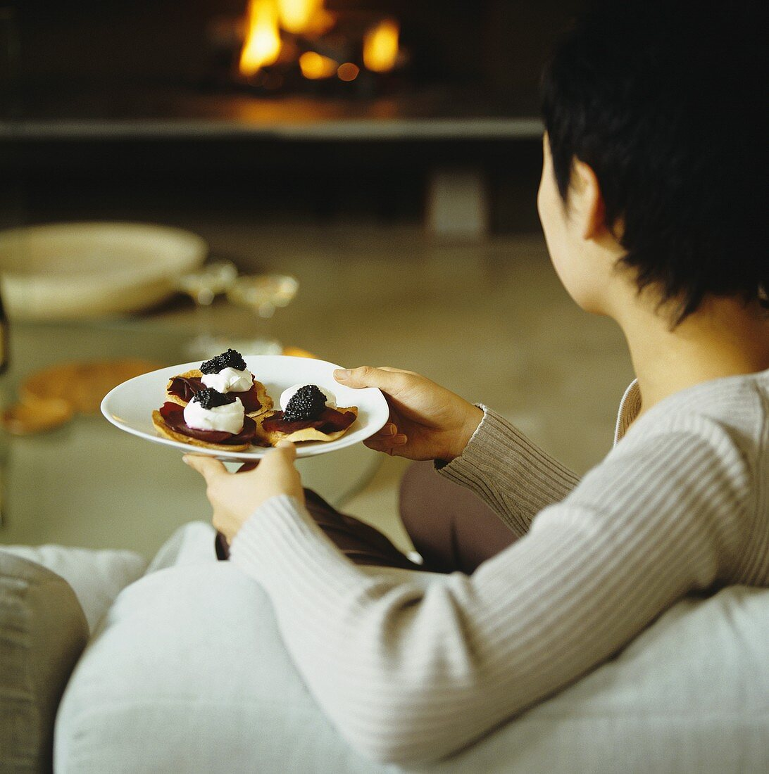 A woman on a sofa with a plate of blinis topped with beetroot and caviar