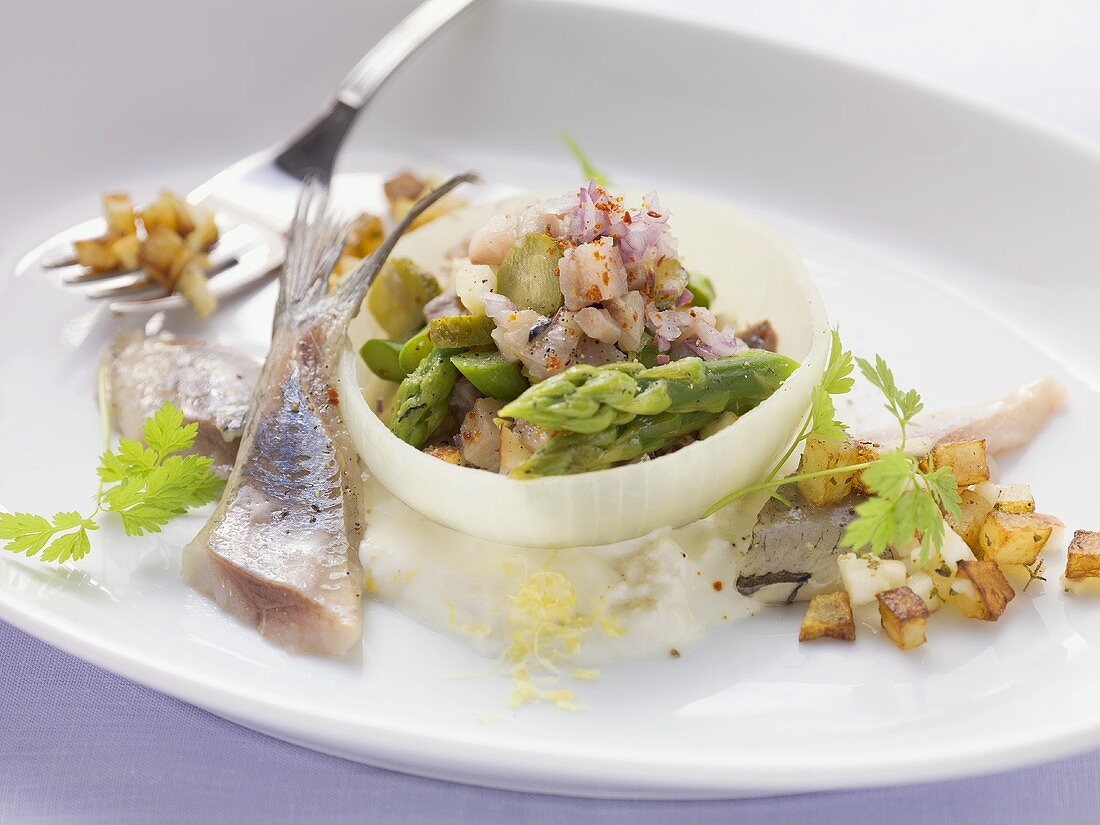 Soused herring tatar with asparagus in an onion ring with a horseradish and apple sauce