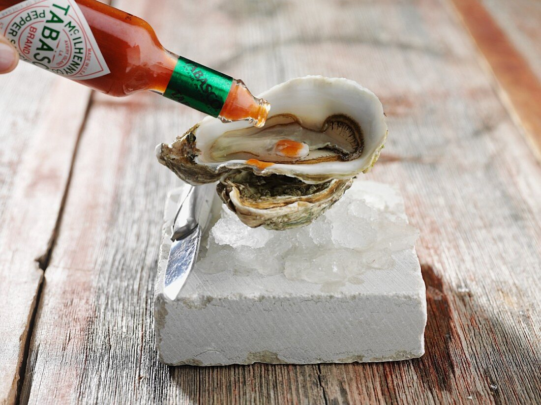Oysters being drizzled with tabasco sauce