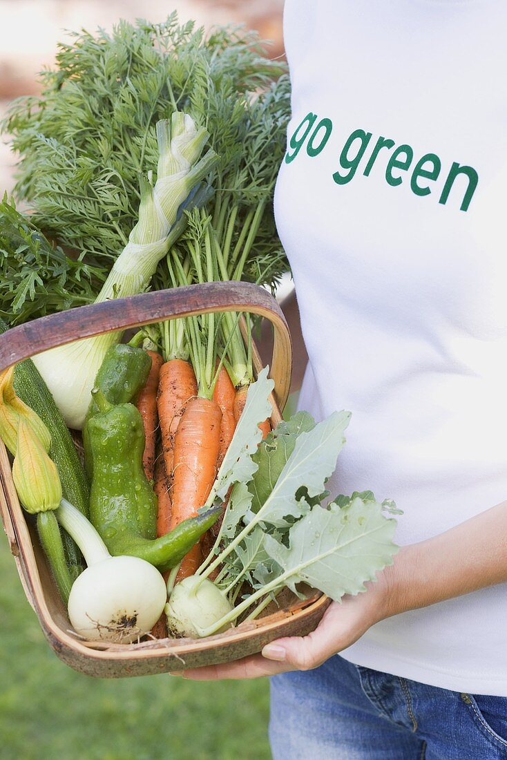A woman holding a basket of freshly harvested vegetables in a garden