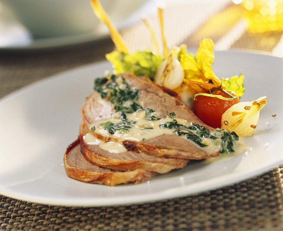 Slices of cold roast pork fillet with herb sauce