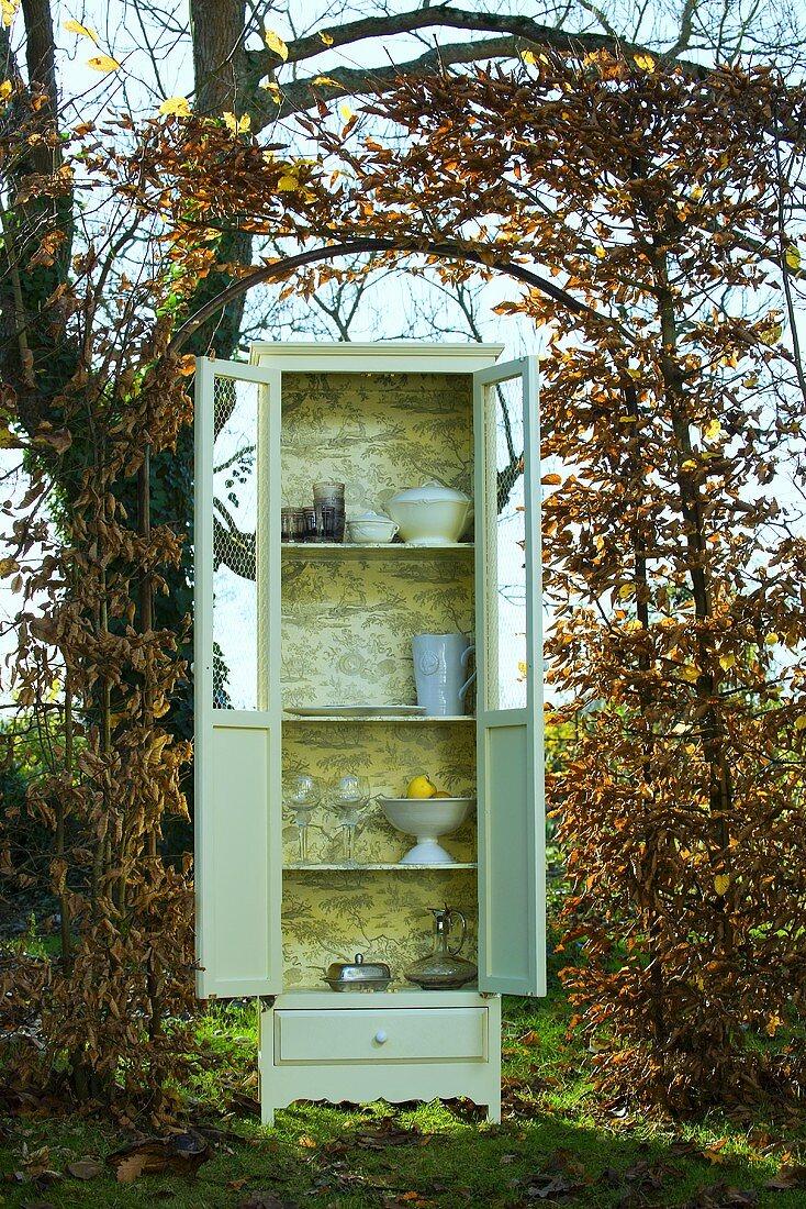 Crockery cupboard in autumnal garden