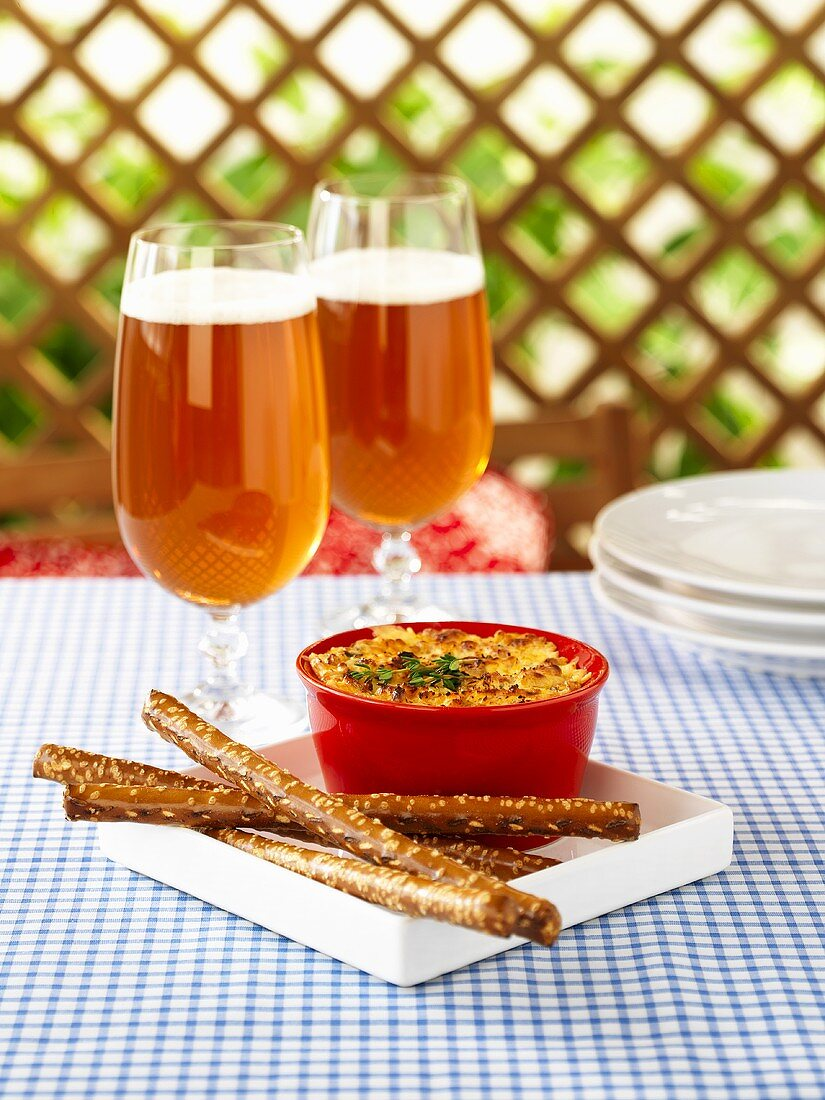 Cheddar cheese and onion dip, salted sticks, glasses of beer