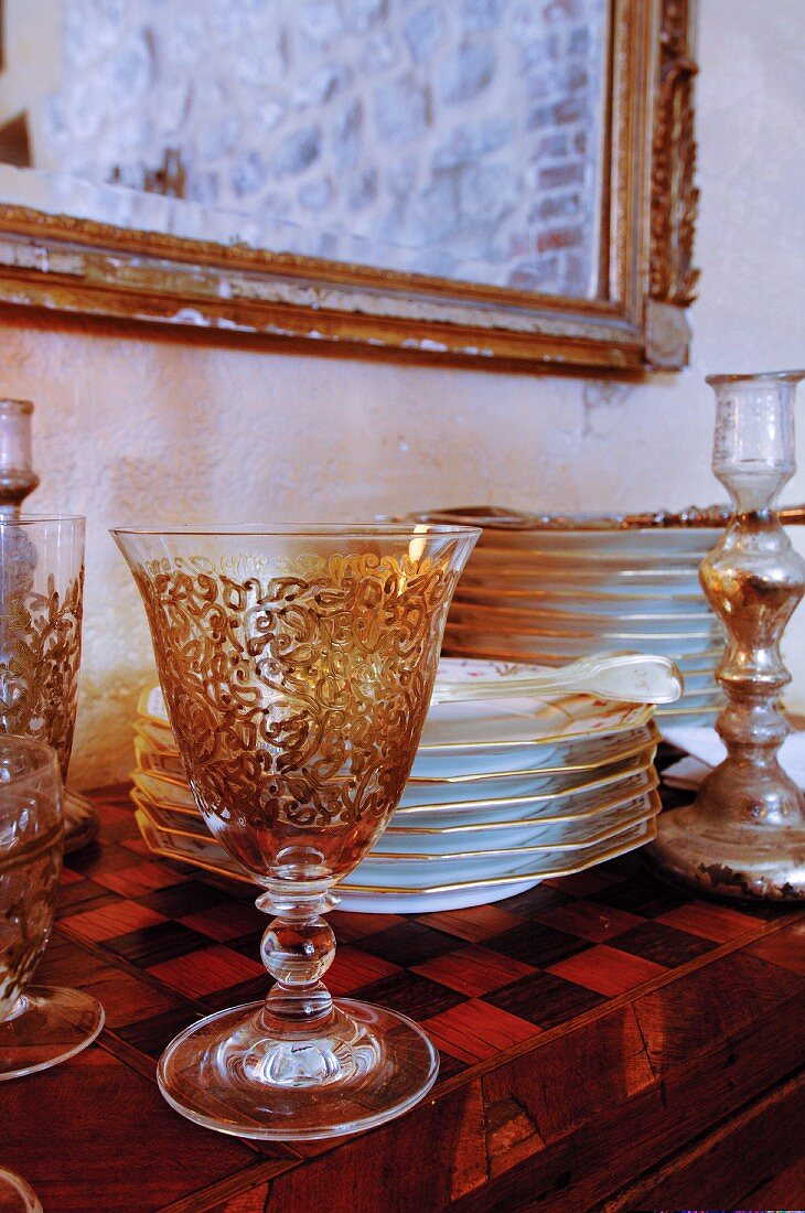 Antique glasses and stacked plates on wall table