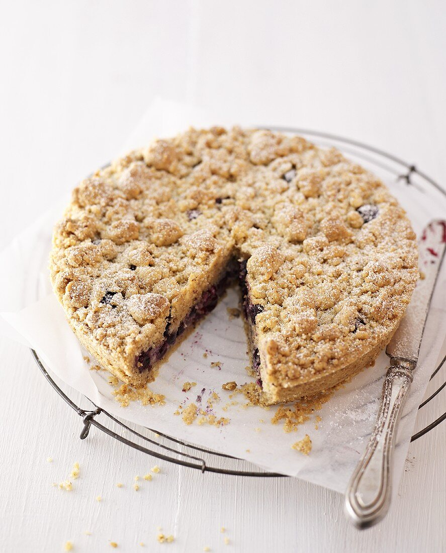Blueberry crumble cake, a piece removed, on cake rack