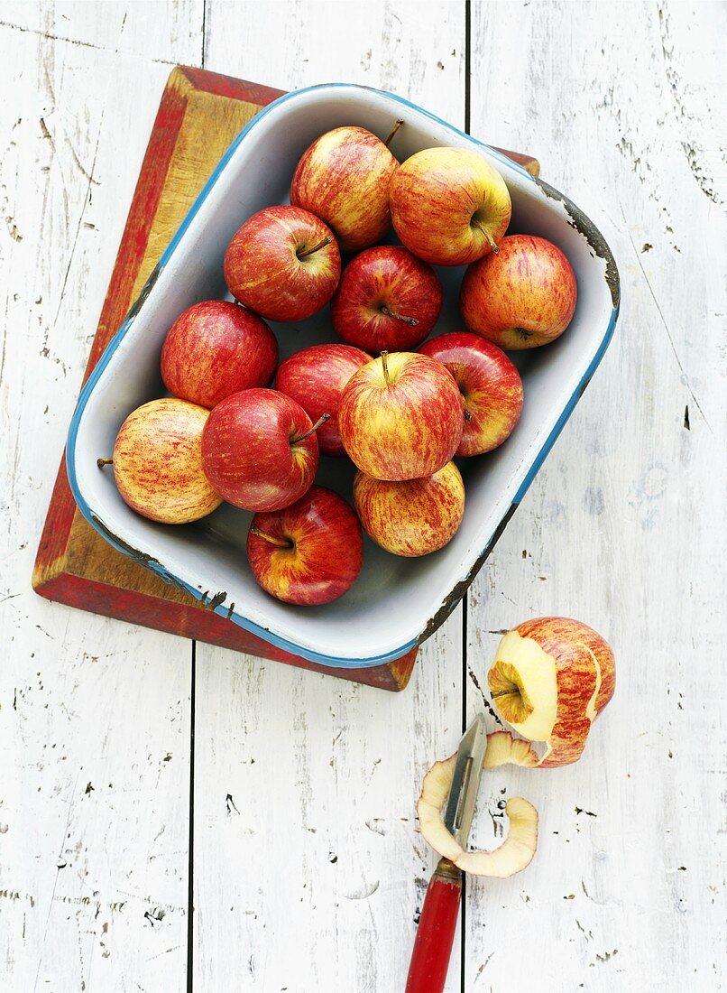 Red apples in enamel dish, half-peeled apple beside it