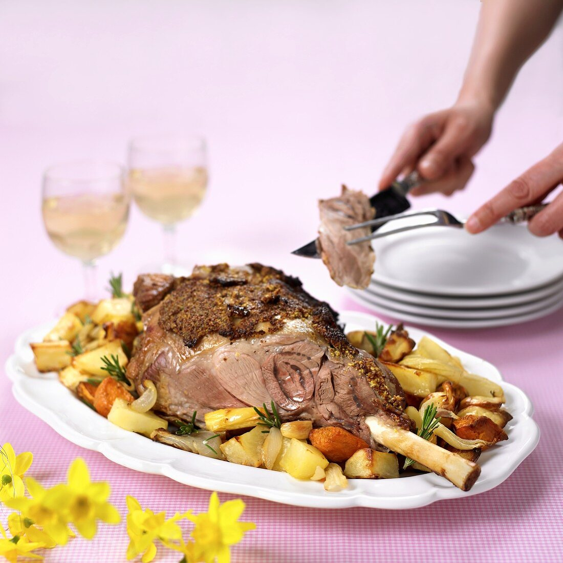 Carving leg of lamb on roasted vegetables