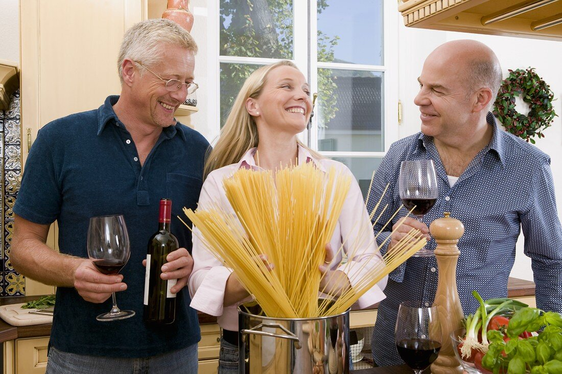 Friends with spaghetti and red wine in kitchen