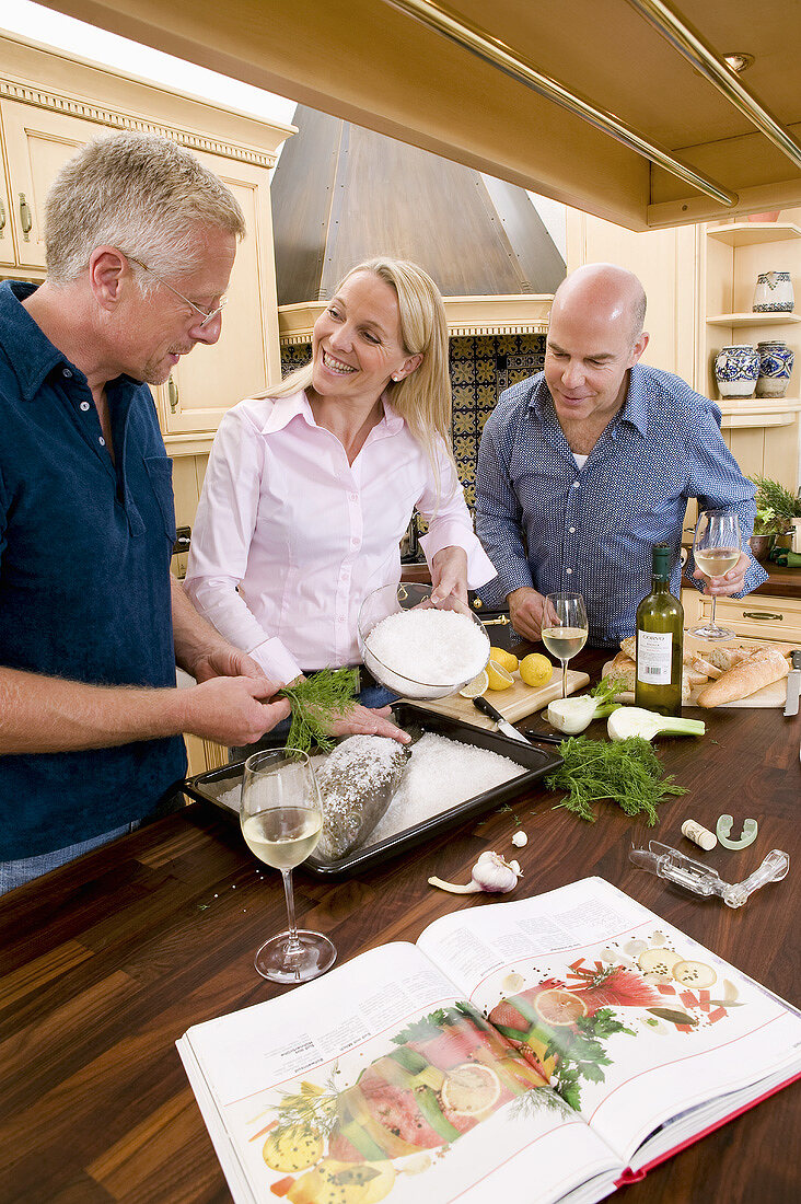 A woman and two men preparing a fish dish together