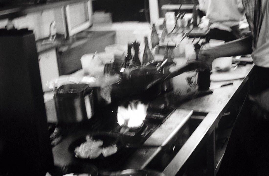 Chef holding a frying pan over a gas flame (b-w shot)