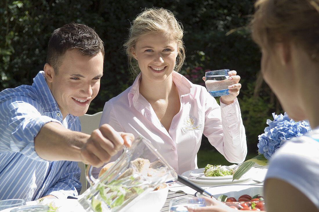 Young people with appetisers & water at table out of doors