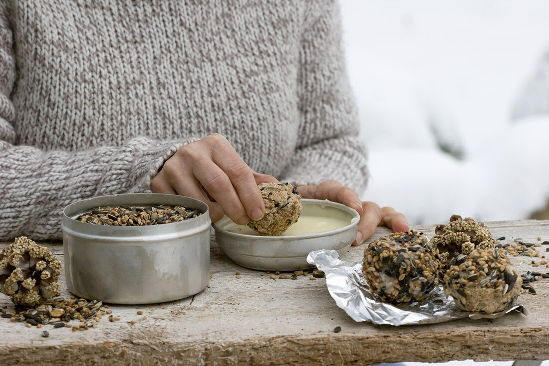 Dipping fat ball in warm palm fat and bird seed