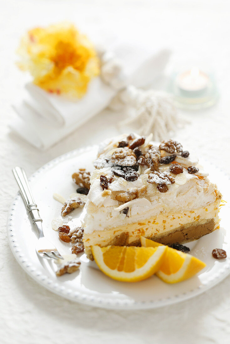A piece of orange cream cake with nuts