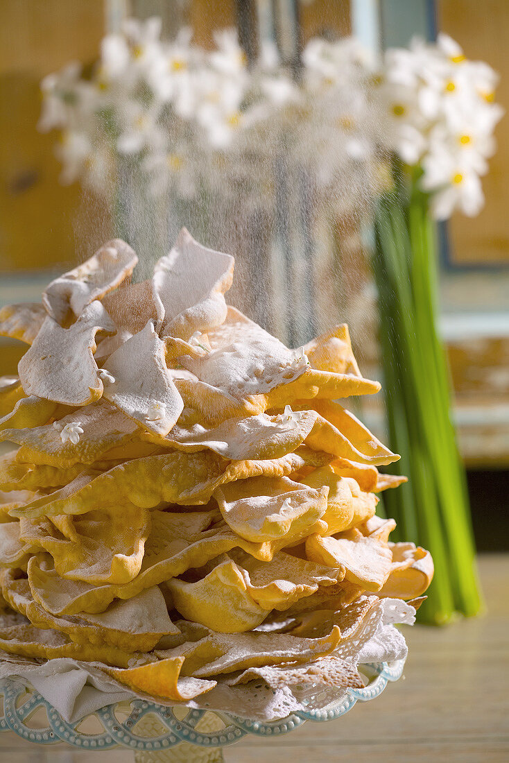 Dusting faworki (Polish fried pastries) with icing sugar