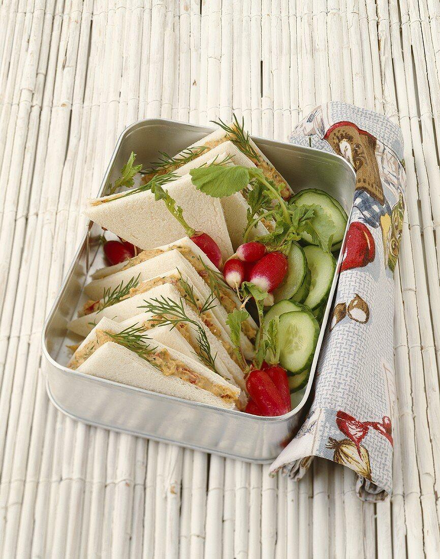 Tuna tramezzini with cucumber and radishes in metal box